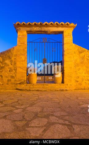 Gateway of the Iglesia de San Juan Bautista church against an evening sky in Deia, Mallorca, Spain. - Stock Image