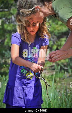 young girl butterfly butterflies mountain lake stream snow spring nets mom - Stock Image