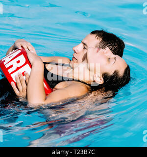 Lifeguard helping a woman after swimming accident. - Stock Image