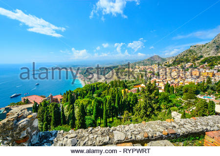 Looking down from the ancient Greek Theatre at Taormina, Italy, on the Italian island of Sicily, with boats and resorts dotting the Mediterranean sea - Stock Image
