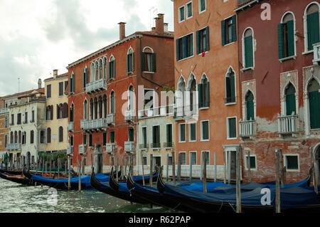 Long shot of buildings along a Venetian canal, with gondolas docked in front - Stock Image