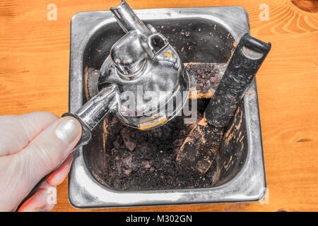 Man's hand on a portafilter handle, emptying brewed coffee grounds / grouts from an espresso machine into a - Stock Image