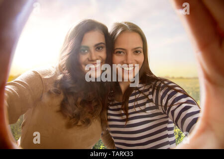 Portrait of two women seen through gap of their hands held together - Stock Image
