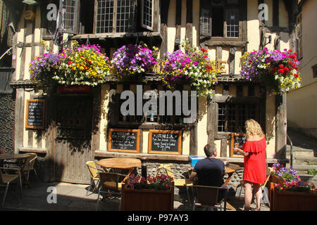 Hastings, UK -July 14 2018: A couple by a pub in George Street in Hastings Old Town on a hot summers day as the temperatures sore to above 27 degrees on 14 July 2018. Hastings on the south coast of England is 53 miles south-east of London and is 8 miles from where the  Battle of Hastings took place in October 1066. Credit: David Mbiyu Credit: david mbiyu/Alamy Live News - Stock Image