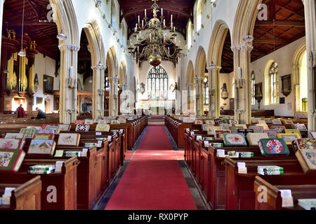 Interior of St. Peter's Church, Tiverton, Devon, UK with pews having decorative individual embroidered kneeler cushions - Stock Image