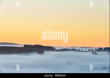 On the border between England and Wales near Knighton, Powys, UK. Evening view west from Stonewall Hill showing the valleys filled with thick fog - Stock Image