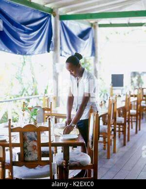 A waitress sets a table at the Lime N Pub. Kingstown, St. Vincent. West Indies. - Stock Image