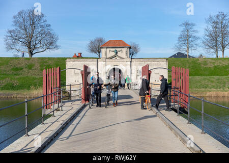People on the bridge leading across the moat to the King's Gate at the Citadel (Kastellet) in Copenhagen, Denmark - Stock Image