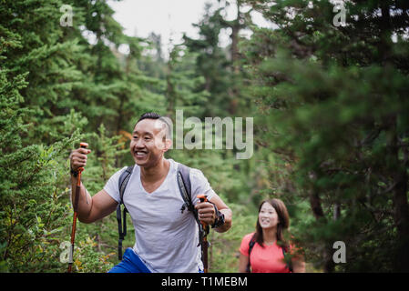 Happy couple hiking in woods - Stock Image