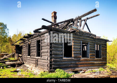 Ruins of a burned down old wooden hut wide angle view - Stock Image