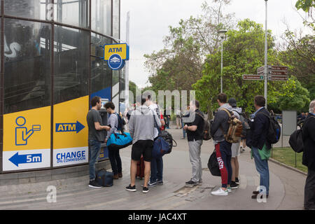 People queuing at an ATM cash machine just outside Prague main railway station - Hlavní nádraží - Stock Image