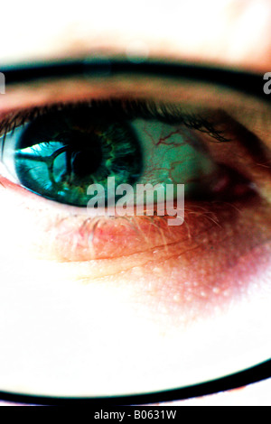 Macro shot of an eye behind glasses. - Stock Image