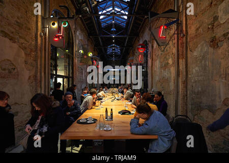 TURIN, ITALY - NOVEMBER 3, 2018: Ogr, Officine Grandi Riparazioni cafe interior with people, evening in Turin, Italy. - Stock Image