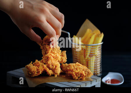 Hand grabs crispy kentucky fried chicken. French fries and tomato on black wooden table - Stock Image