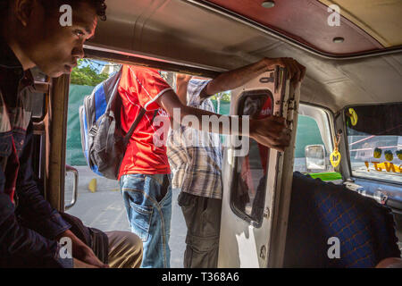 Dili, Timor-Leste - Aug 10, 2015: A teenage boy and other men inside a mikrolet bus driving with an open door, East Timor. Micro let minibus dangerous - Stock Image