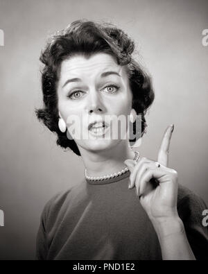 1950s 1960s BRUNETTE WOMAN PEARL STRAND EARRINGS POINTING FINGER UP SPEAKING TALKING LOOKING AT CAMERA LECTURE TEACH NAG - g4859 HAR001 HARS EXPRESSIONS B&W CONCERNED LECTURE EYE CONTACT BRUNETTE HEAD AND SHOULDERS NAGGING STYLES UP AUTHORITY HOUSEWIVES OCCUPATIONS TEACH SPOKESPERSON FAUX STYLISH SELF ASSURED STRAND COSTUME JEWELRY FASHIONS MID-ADULT MID-ADULT WOMAN NAG BLACK AND WHITE CAUCASIAN ETHNICITY EXPRESSIVE HAR001 OLD FASHIONED - Stock Image