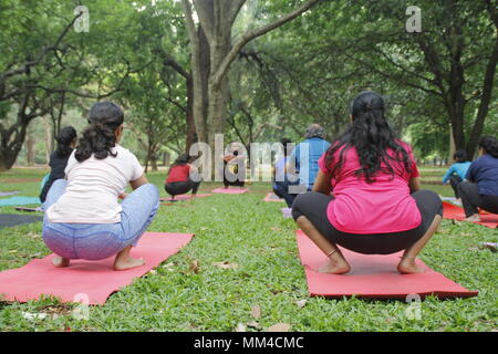 Group of young men and women performing yoga in Cubbon park, Bangalore. - Stock Image