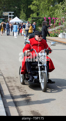 London,UK,20th May 2019,Chelsea Pensioner rides on a three wheeler motorbike at the RHS Chelsea Flower Show on Press Day which takes place before it officially opens tomorrow until Saturday 25th May. The world renowned flower show is a glamorous, fun and an educational day out which is attended by many celebrities. There are many gardens, floral displays, Marquees all set in the glorious grounds of The Royal Hospital Chelsea.Credit: Keith Larby/Alamy Live News - Stock Image