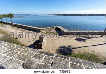 A young man sits on a point of the seawall at the Castillo de San Marcos, a Spanish fortification at St. Augustine, Florida USA - Stock Image