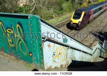 Graffiti vandalism on a pedestrian footbridge over the railway. Cheltenham, Gloucestershire, UK. - Stock Image