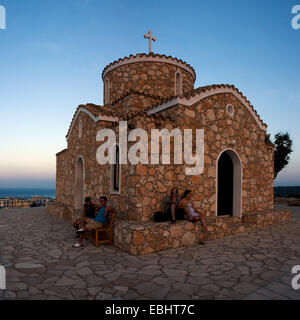 Tourists sitting outside the church of Prophet Eliah (Profitis Ilias) by sunset. City of Protaras, Cyprus. - Stock Image