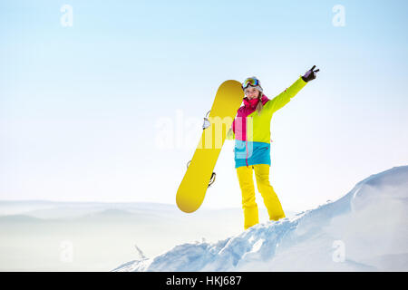 Happy girl snowboarder copyspace top mountain - Stock Image