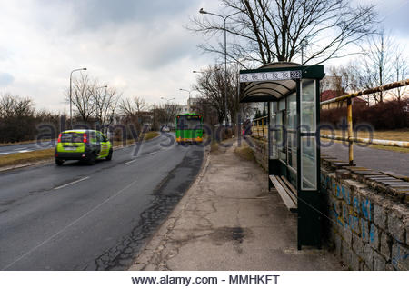 Bus stop on the Inflancka street with driving car and bus on a cloudy day in Poznan, Poland - Stock Image