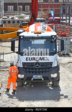 Euromix delivery lorry truck & driver placing concrete into vertical pumping boom rig to roof level on confined construction building site London UK - Stock Image