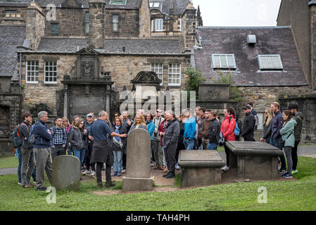 Tourists on a walking tour of Edinburgh's visit the grave of John Gray, the master of Greyfriars Bobby, in Greyfriars Kirkyard. - Stock Image