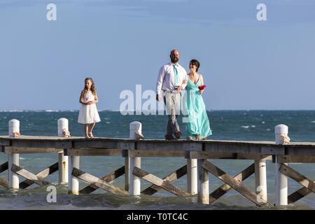 Just Married Couple walking on Fishing Dock Pier followed by Daughter in Caye Caulker, a small Caribbean Island in Central American Country Belize - Stock Image