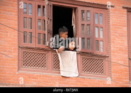 A young Nepali couple peer outside the window of their modern house. Bhaktapur, Nepal. - Stock Image