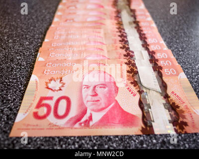 A line of Canadian 50 dollar bills: A long line of Canadian fifty dollar bills spread out on a counter. - Stock Image