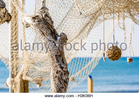 Dry white branches and fishing net, at background blue mediterranean sea on a a sunny day - Stock Image