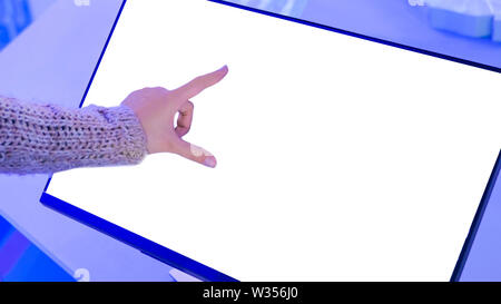 Woman using interactive white blank touchscreen display terminal at scifi show - Stock Image
