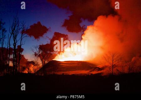 Lava and ash pour out from the summit of the Kilauea volcano crater following the collapse July 6, 2018 in Hawaii. The recent eruption continues destroying homes, forcing evacuations and spewing lava and poison gas on the Big Island of Hawaii. - Stock Image