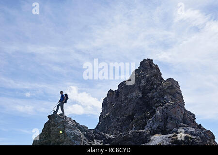 Hiker on peak of rock, Mont Cervin, Matterhorn, Valais, Switzerland - Stock Image