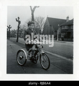 Little boy on a tricycle in a suburban street. - Stock Image