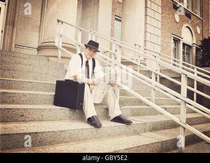 A vintage business man is sitting on the steps of an office building reading the newspaper and thinking for a investment - Stock Image