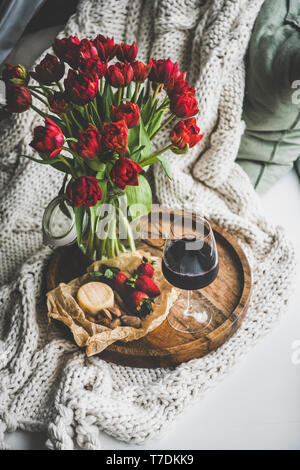 Wine snack set with flowers. Glass of red wine, cheese, roasted almonds, strawberries and bouquet of fresh Spring red tulips on wooden tray over white - Stock Image
