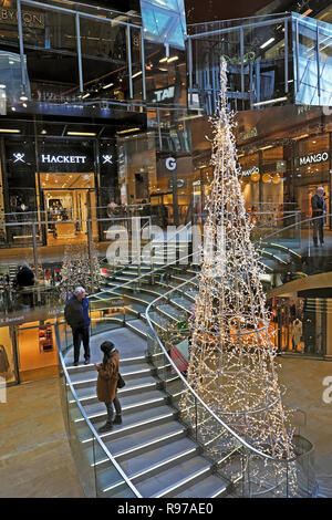 One New Change 2018 Christmas tree and shoppers on staircase inside interior building vertical view in London England UK  KATHY DEWITT - Stock Image