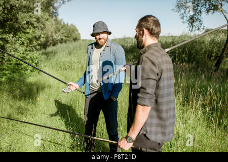 Fishermen walking on the green lawn - Stock Image