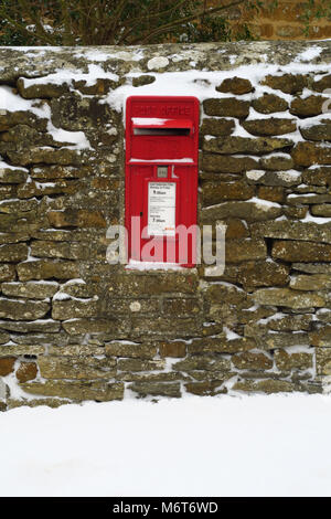 Post box after a March snowfall, Netting Street, Hook Norton, Oxfordshire - Stock Image