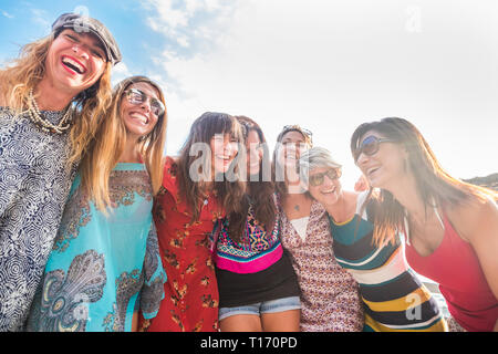 group of seven nice and beautiful caucasian girls young women have fun and laugh and smiles outdoor during the sunset. backlight people enjoying the f - Stock Image
