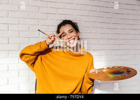 Lovely artistic woman holding color palette for painting indoors over white wall - Stock Image