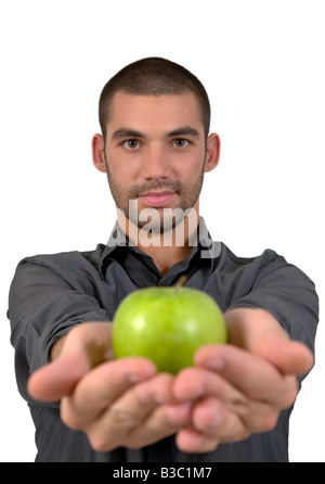 Handsome young man smiling holding a green crispy apple in the palm of his hands on an isolated white background - Stock Image