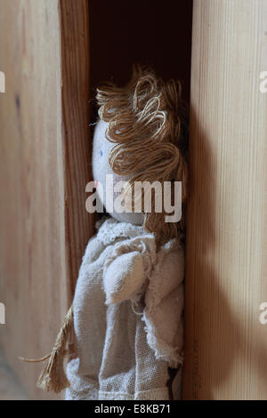 A rag doll is stuck in a wooden cabinet. - Stock Image