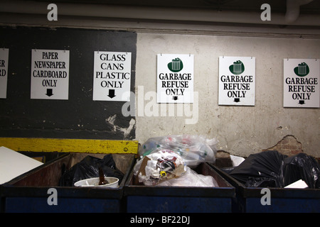 Variety of recycling signs and bins in the back of a restaurant, New York, NY, USA - Stock Image