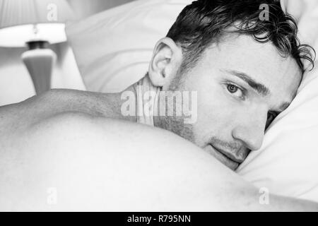 Black and white portrait of good looking man lying on hotel room pillow looking at camera - Stock Image
