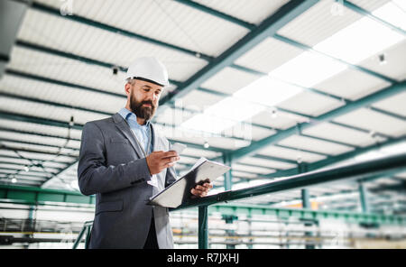 A portrait of a mature industrial man engineer with clipboard and smartphone in a factory, texting. Copy space. - Stock Image