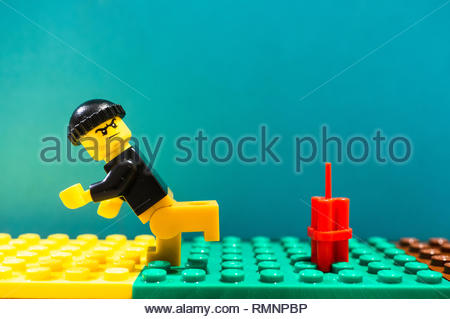 Poznan, Poland - February 13, 2019: Lego man with hat running away from dynamite ready to explode soon. Man is fleeing creating a act of terrorism. - Stock Image